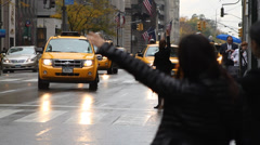 Women trying to hail a cab in rain, 5th Avenue, New York City Stock Footage