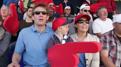 Boy with family in crowd of sports spectators. Could be a stadium crowd at the - stock footage