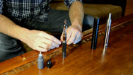 Stock Video Footage of Man filling an electronic cigarette with e-juice.