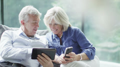Attractive mature couple with technology shopping on the internet at home - stock footage
