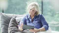 Attractive mature woman with computer tablet browsing the internet at home - stock footage