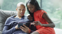 Attractive young couple with technology shopping on the internet at home - stock footage