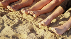 Group of young people with feet in sand, closeup - stock footage