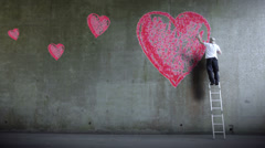 Graffiti artist expressing himself by drawing on the wall. Love heart graffiti. Stock Footage