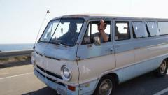 Group of young people on road trip driving old van - stock footage