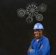 african black man worker with chalk gears blackboard - stock photo
