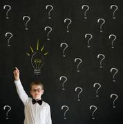 pointing boy dressed up as business man questioning ideas - stock photo