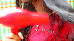 Woman using a hair dryer Stock Footage