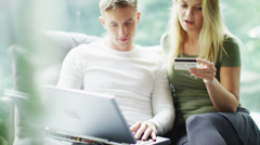 Attractive young couple with laptop shopping on the internet at home - stock footage