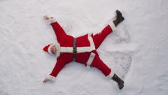 High angle shot of Santa Claus making a snow angel Stock Footage