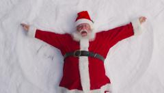 Santa playing in the snow. Overheard shot. - stock footage