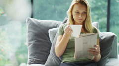 Attractive young woman relaxing at home with newspaper and cup of coffee - stock footage