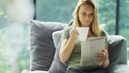 Stock Video Footage of Attractive young woman relaxing at home with newspaper and cup of coffee
