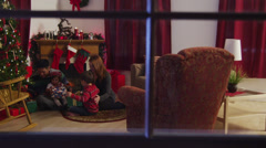 Stock Video Footage of Looking into window at family enjoying Christmas