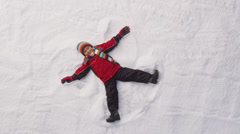 Young boy makes a snow angel. Overhead shot. - stock footage
