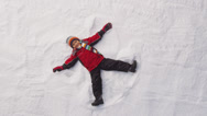 Stock Video Footage of Young boy makes a snow angel. Overhead shot.