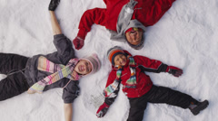 Family laying in winter snow, overhead shot Stock Footage