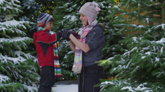 Mother helping young son get ready to play in snow Stock Footage