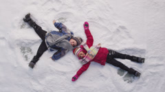 Two kids in winter making snow angels - stock footage