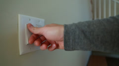 A hand using the light switches Stock Footage