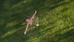 Child playing in sprinkler, overhead shot Stock Footage