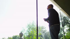 Attractive man in modern glass home takes a look at the view outside Stock Footage