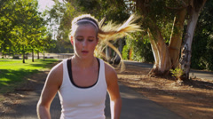 Young woman jogging in park - stock footage