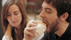 Happy girl and a guy eating burgers Stock Footage