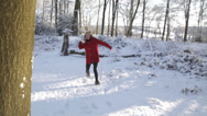 Stock Video Footage of Snowball fight with Little Red Riding Hood - Young girl in red coat stands out