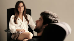Young man speaking to a therapist while she is taking notes Stock Footage