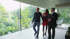 Young couple being shown round a luxury modern home by the estate agent - stock footage