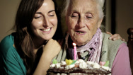 Stock Video Footage of Happy smiling grandmother celebrating and giving a birthday cake to her grandson