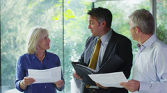 Mature couple being shown round a luxury modern home by the estate agent - stock footage