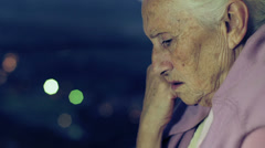 Pensive and depressed  old woman looking out window in the night  - stock footage