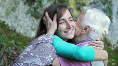 Grandmother and granddaugh giving each other a cuddle full of love and affection - stock footage