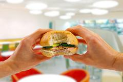 hands hold a burger in fast food restaurant - stock photo