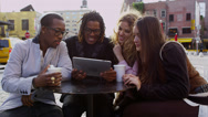 Stock Video Footage of Group of friends looking at digital tablet together