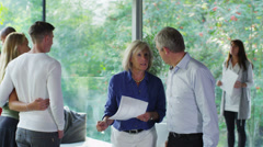 Mature couple talking to estate agent at open viewing of luxury modern home Stock Footage