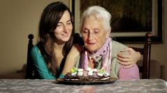 Old and young woman blow out her birthday candles. - stock footage