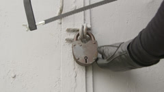 Burglar breaks padlock on the gate Stock Footage