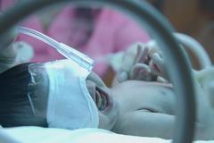 premature baby with oxyzen  under ultraviolet lamp in the incubator - stock photo