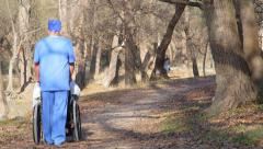 Male nurse pushing recovering patient on wheelchair Stock Footage