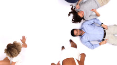 Circle of young people in white studio looking up at camera shot from above. Stock Footage