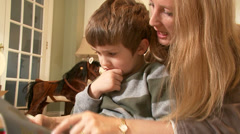 A cute young boy concentrates as his mother teaches him to read. Close up. Stock Footage