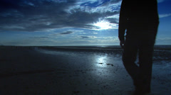 Man alone, walking along the beach at sunset. High quality HD video footage Stock Footage