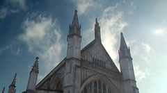 Timelapse shot of clouds moving across a blue sky against the roof of a church. Stock Footage
