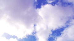 Timelapse of fluffy white clouds drifting across a blue sky overhead - stock footage