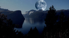 Peaceful scene with huge moon over mountains Stock Footage