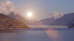 Timelapse of the sun rising above a spectacular landscape of lake and mountains. Stock Footage