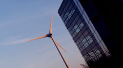 Wind turbine set against the side of a modern generic office building providing Stock Footage